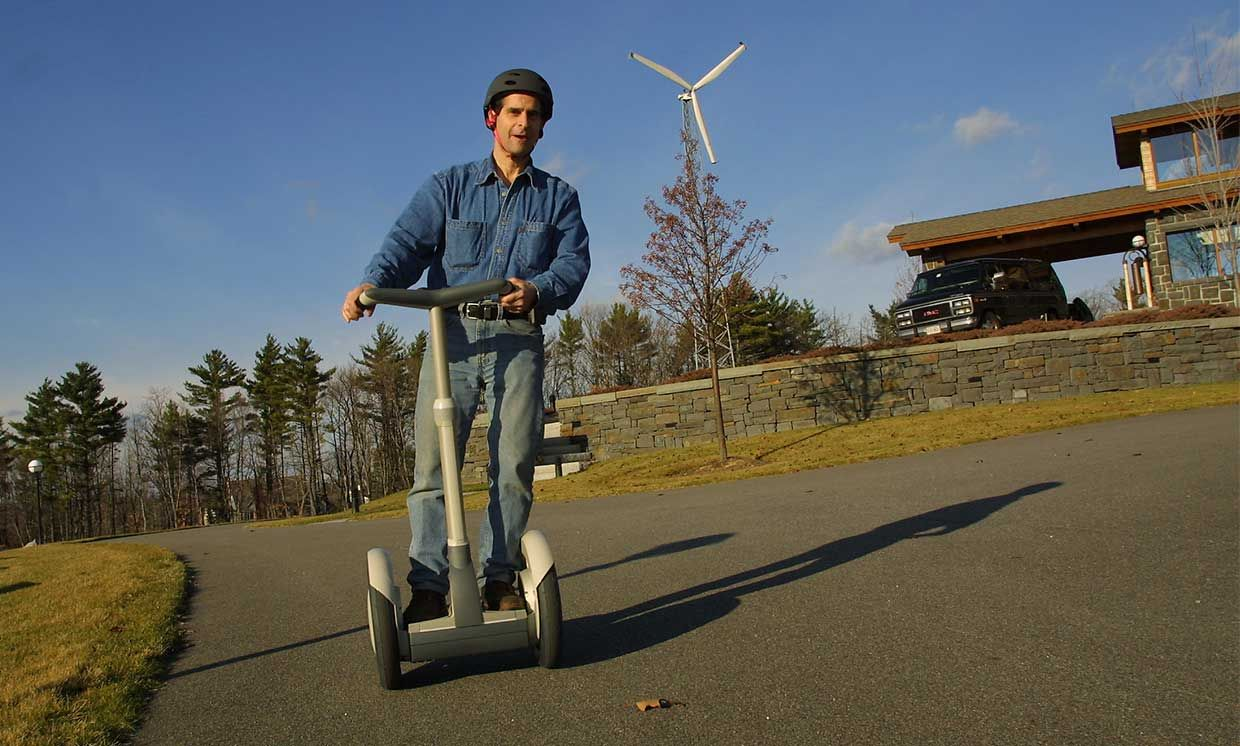 2002 photo of Dean Kamen, inventor of the Segway Human Transporter, riding a Segway outside his home and showing off it's self-balancing design.