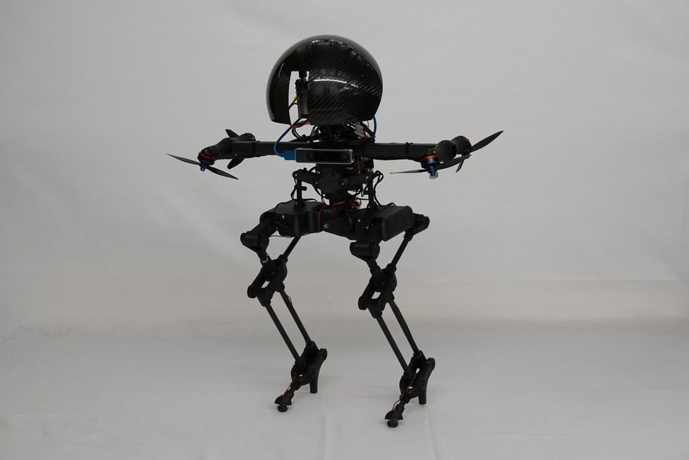 A black bipedal robot with a round head and four thrusters standing on the ground