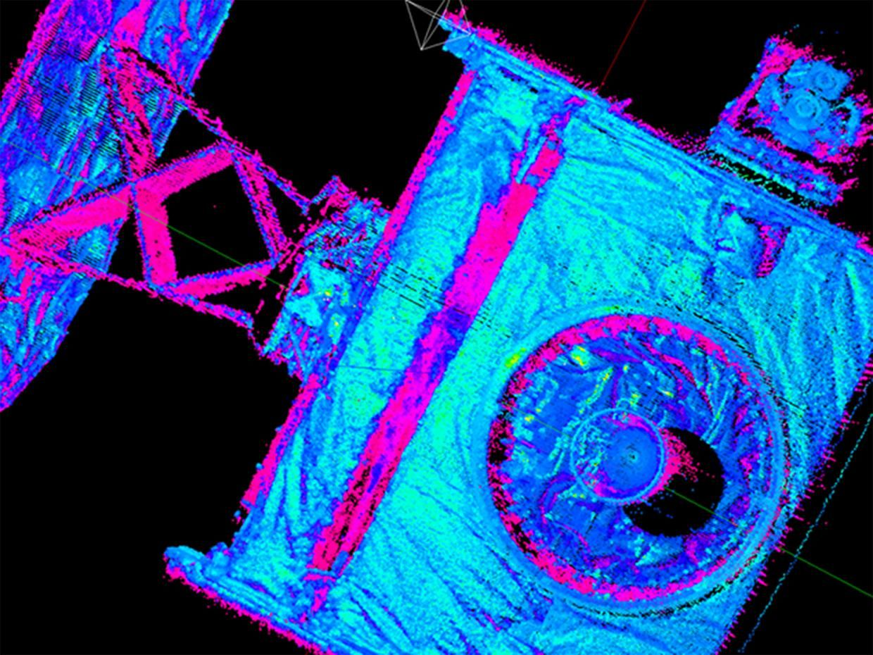 A blue and violet image of a boxy structure with a large strut against a black backgronf