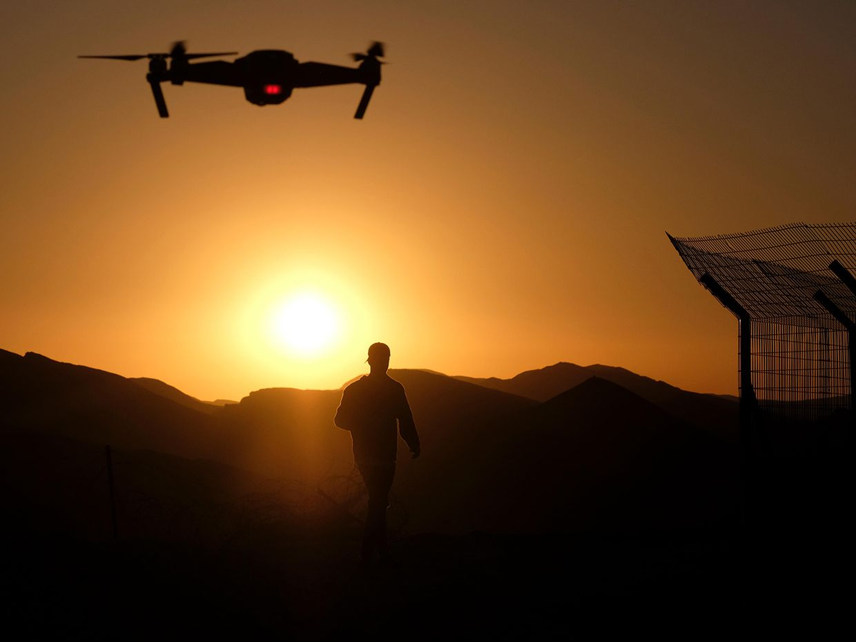 A camera equipped radio controlled quadcopter drone flying over a silhouetted man.