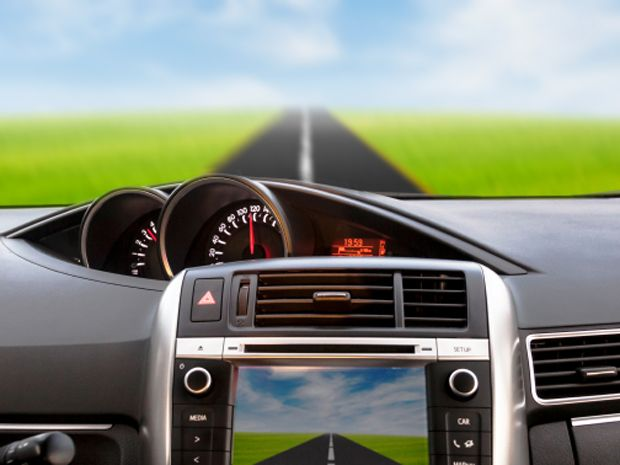 A car dashboard with a road and green fields in the windshield and on the car's display.