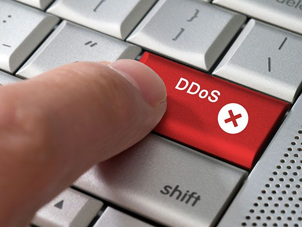 """A close-up image of a finger pushing a red key titled """"DDoS,"""" which stands for distributed denial-of-service attacks, on a white keyboard."""
