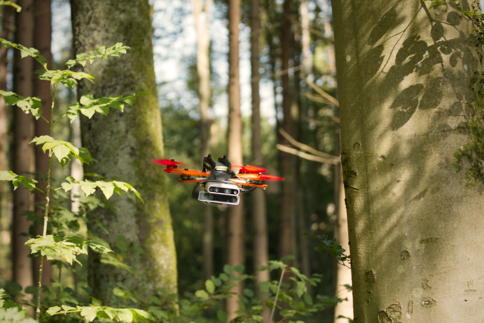 A colorful quadrotor drone flies through a forest
