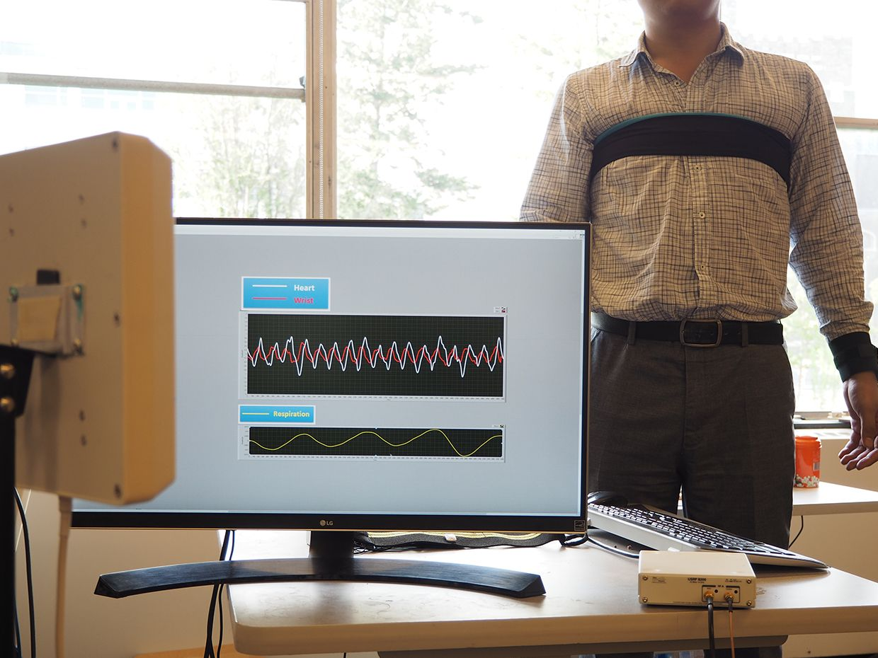 A computer and equipment in the foreground show the monitoring of vital signs for a patient in the background with black straps around his chest and wrist.