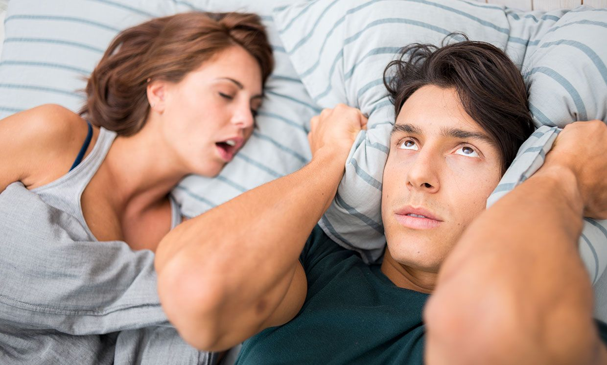 A couple in bed. The woman is snoring, and the man is covering his ears with a pillow.