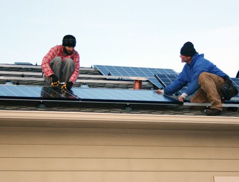 A crew from REC Solar installs solar panels on the roof of the author's garage.