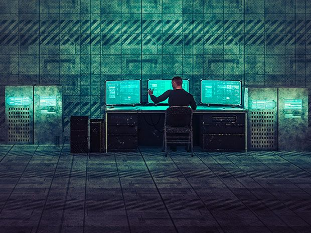 A figure in black inputs commands into a computer screen in the corner of an industrial facility.
