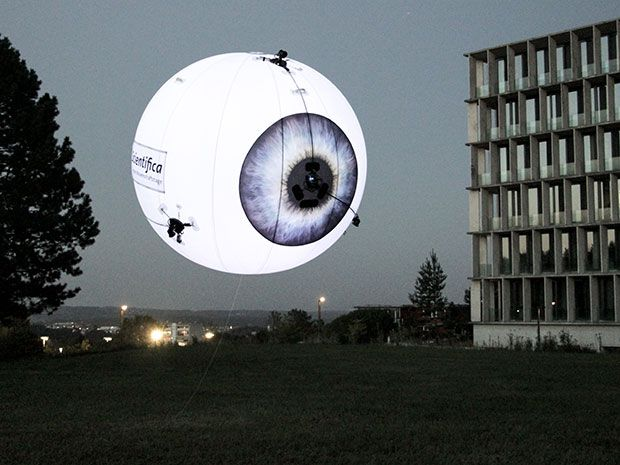A glowing floating balloon patterned to look like an eyeball hovers in the evening sky outdoors.
