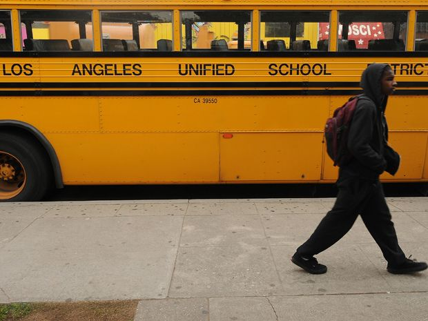 A kid in front of a school bus.