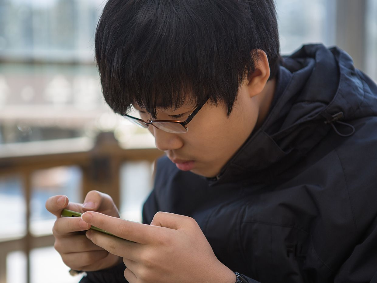 A Korean teenager staring intently at a smartphone.