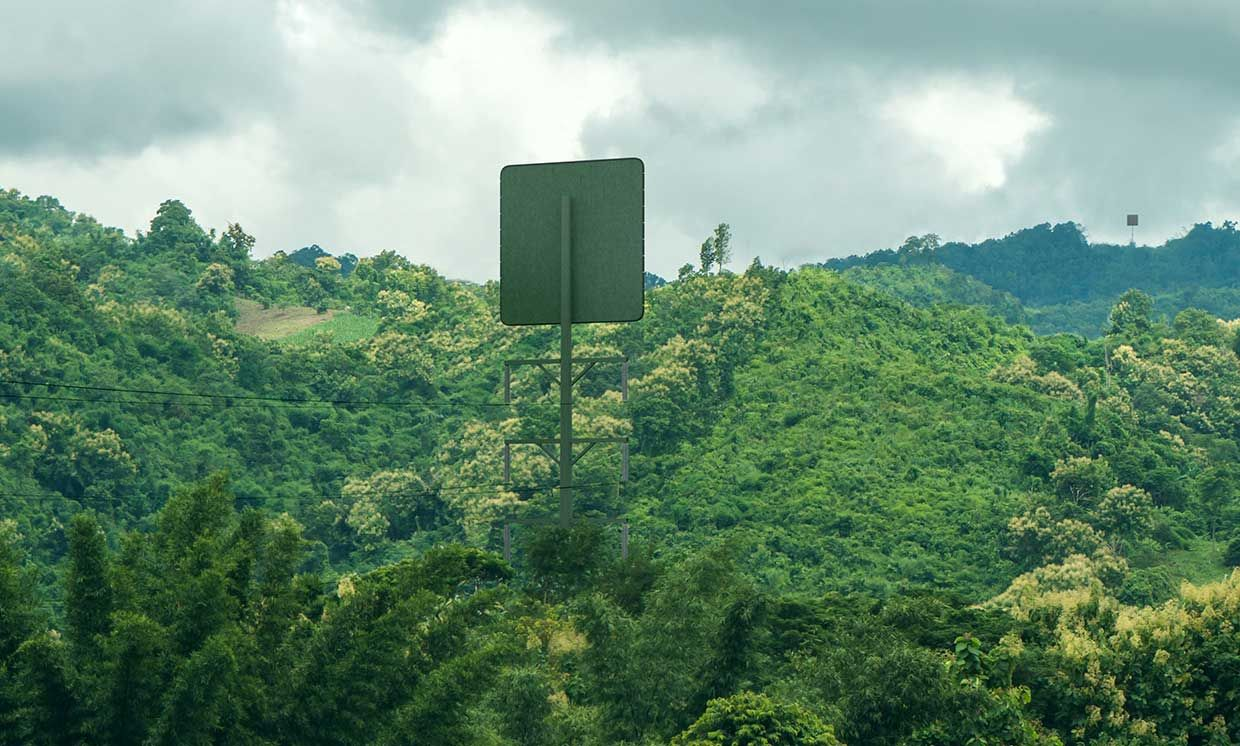 A large square panel is located atop a tall pole into a hilly area dense with vegetation. On a distant hill, another square panel atop a pole can be seen.