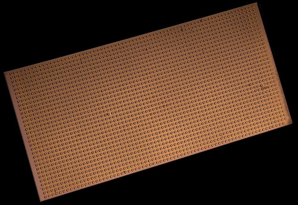 A magnified view of a gold rectangular chip with evenly spaced dots densely covering its surface