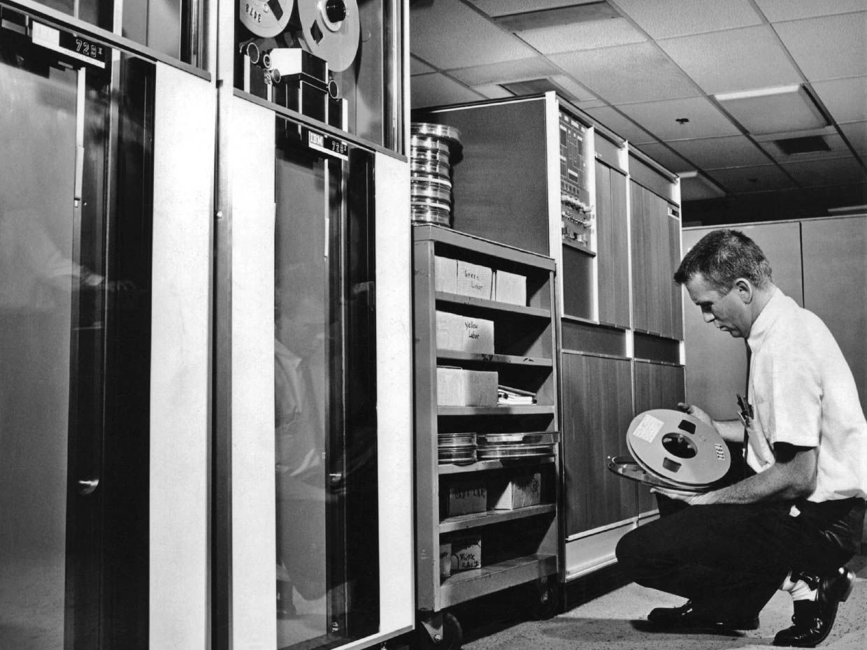 A man holding a magnetic reel in front of an old computer.