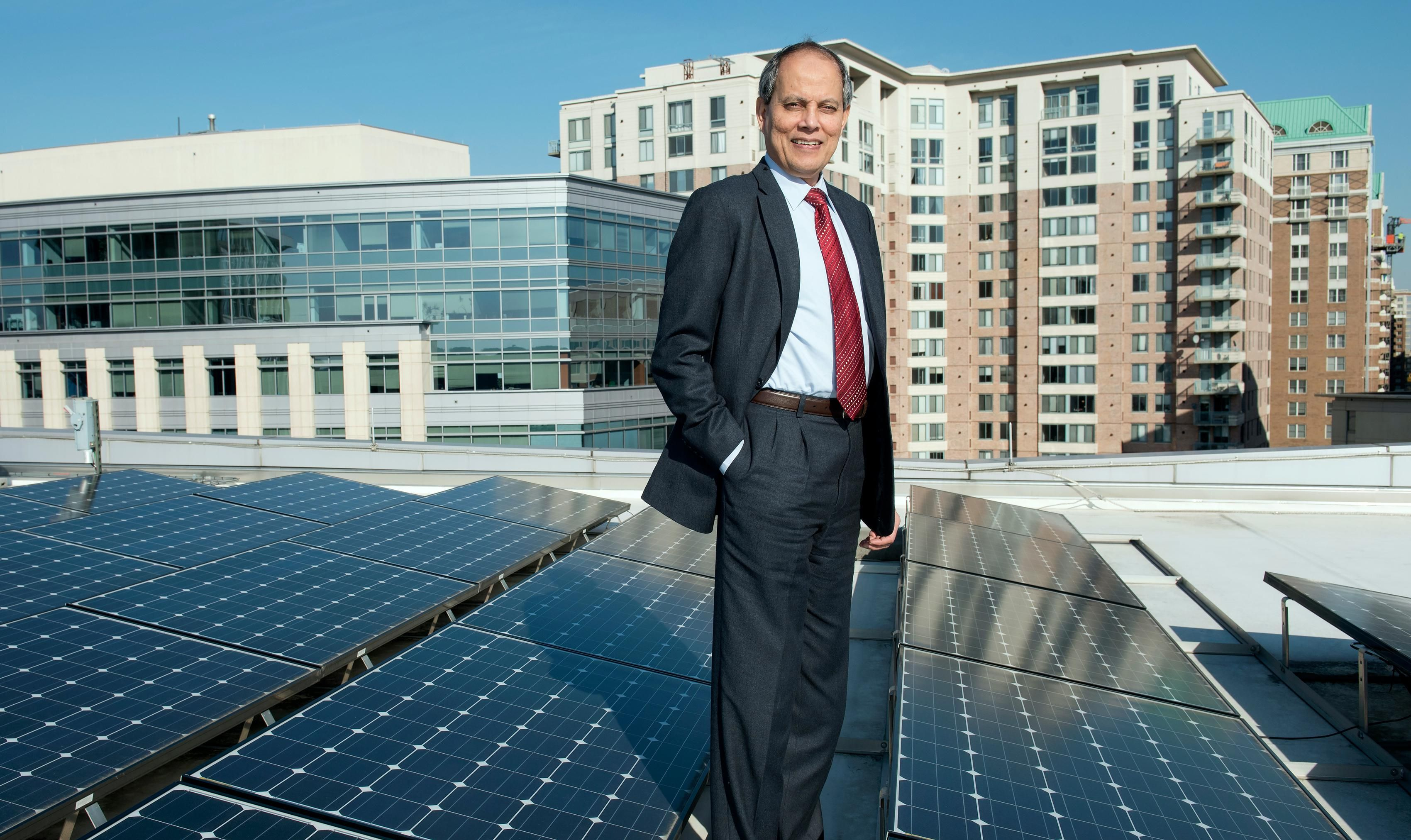 A man in a suit stands amidst a rooftop solar installation, with buildings behind him.