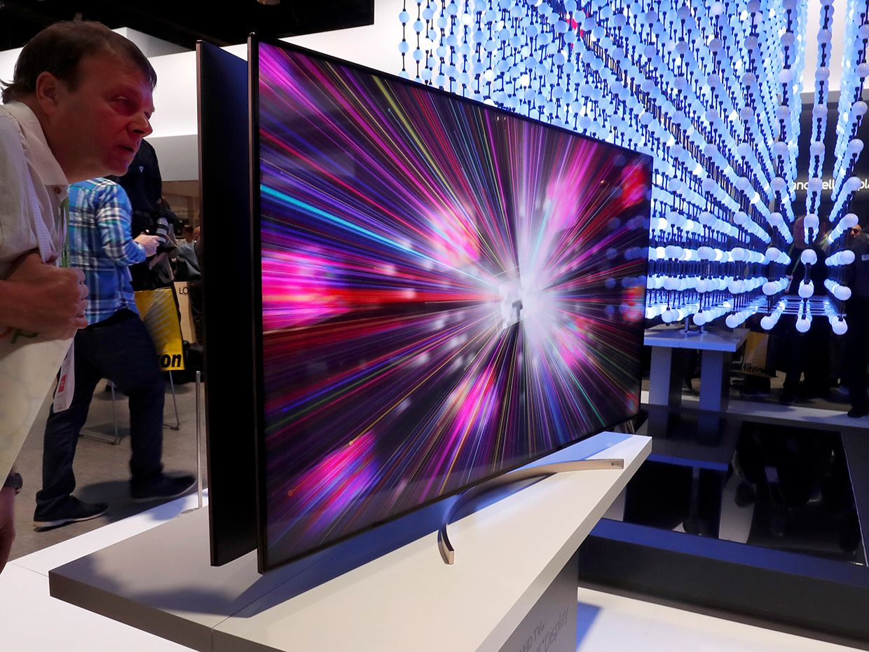 A man looks over a 4K Super UHD TV Nano Cell display in the LG Electronics booth at the Las Vegas Convention Center during the 2018 CES in Las Vegas, Nevada, U.S. January 9, 2018
