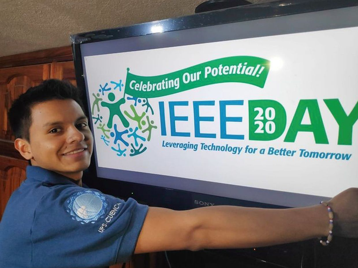 A man standing in front of a IEEE day sign.