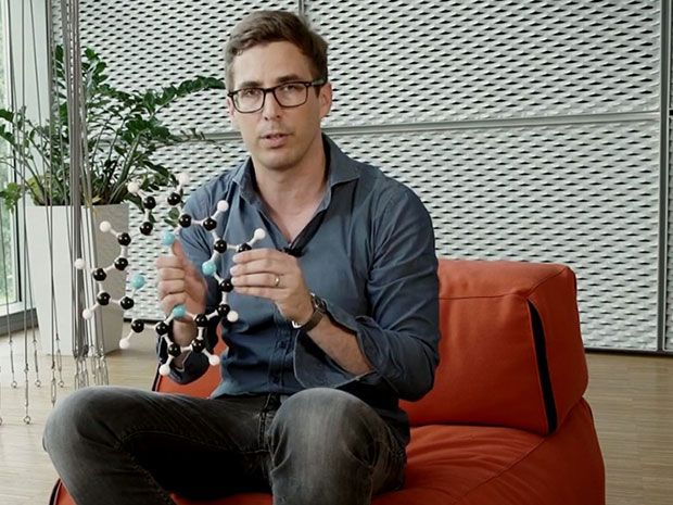 A man wearing black jeans and a grey-blue shirt sits holding a model of a ring-shaped molecule
