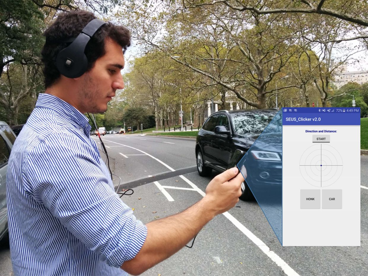 A man wears headphones and look at a screen in front of him while a car passes on a nearby street.