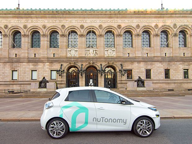 A NuTonomy self-driving taxi in front of a grand-looking building, the Boston Public Library