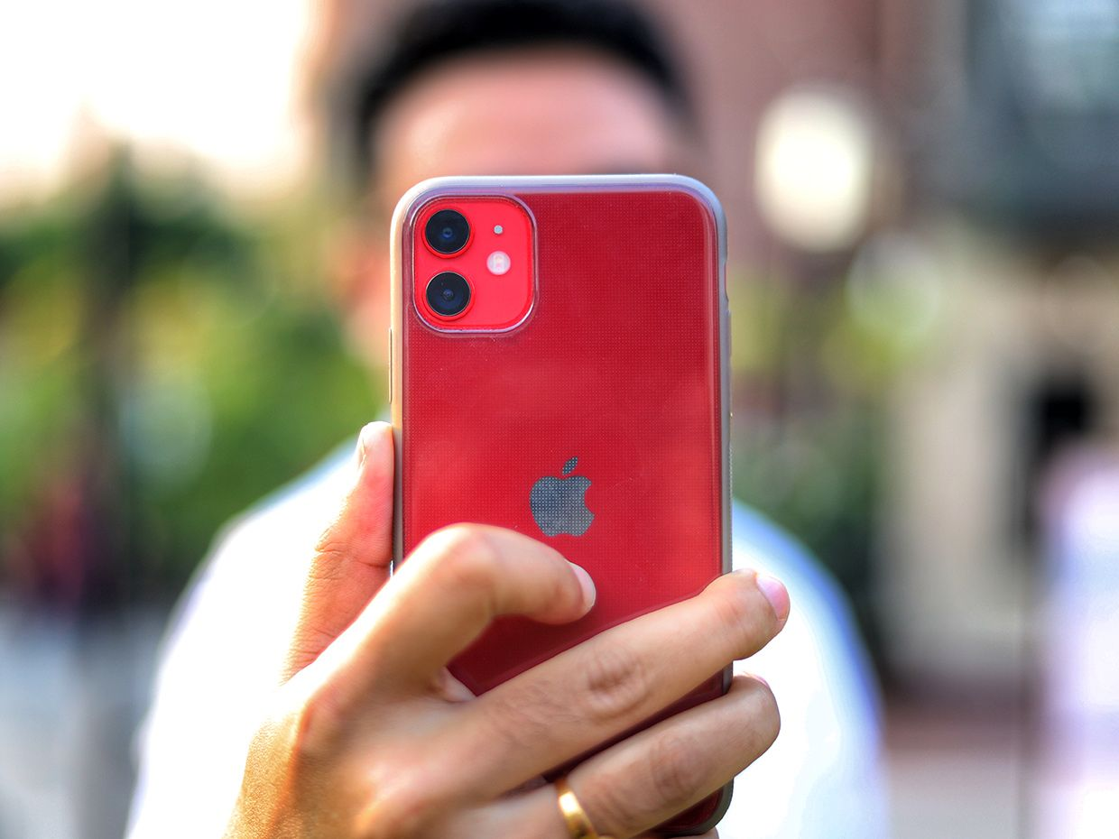 A person holds up a red iPhone to the camera.