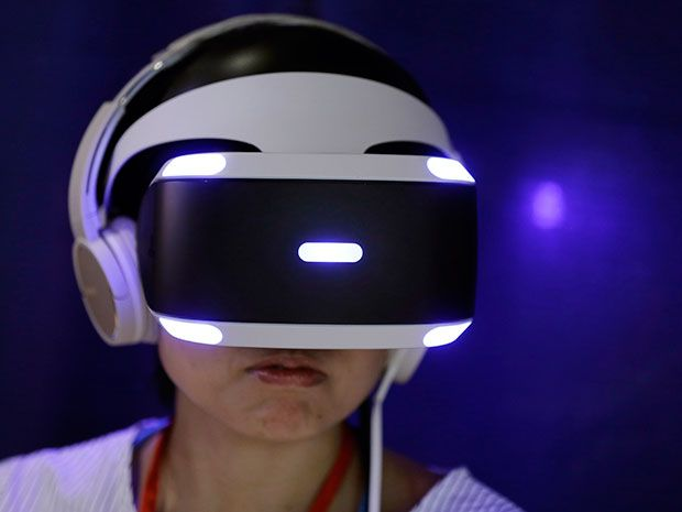 A person wears a white-and-black Sony PlayStation VR headset to play a video game during a launch event in Tokyo, Japan.