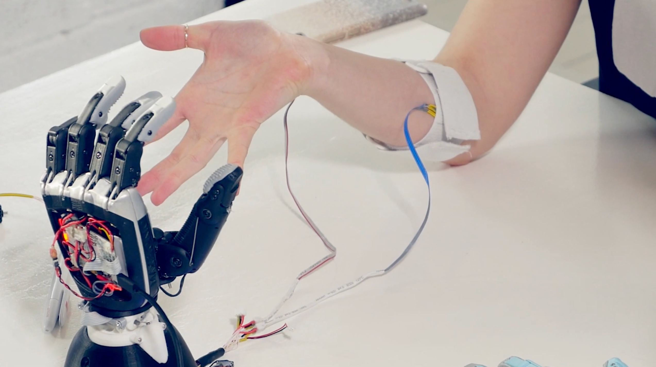 A person with sensors attached to their arm controls a robotic hand