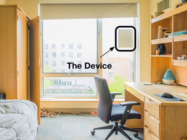 A photo illustration shows a laptop-sized device that monitors sleep patterns mounted to a window in a home office