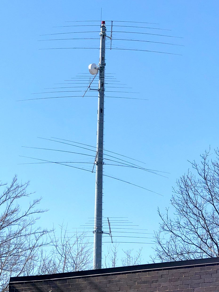 A photo of a cell tower with multiple levels of antennas sticking out of it.