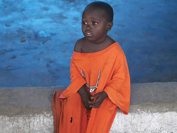 A photo of a Liberian child sitting in an Ebola isolation ward