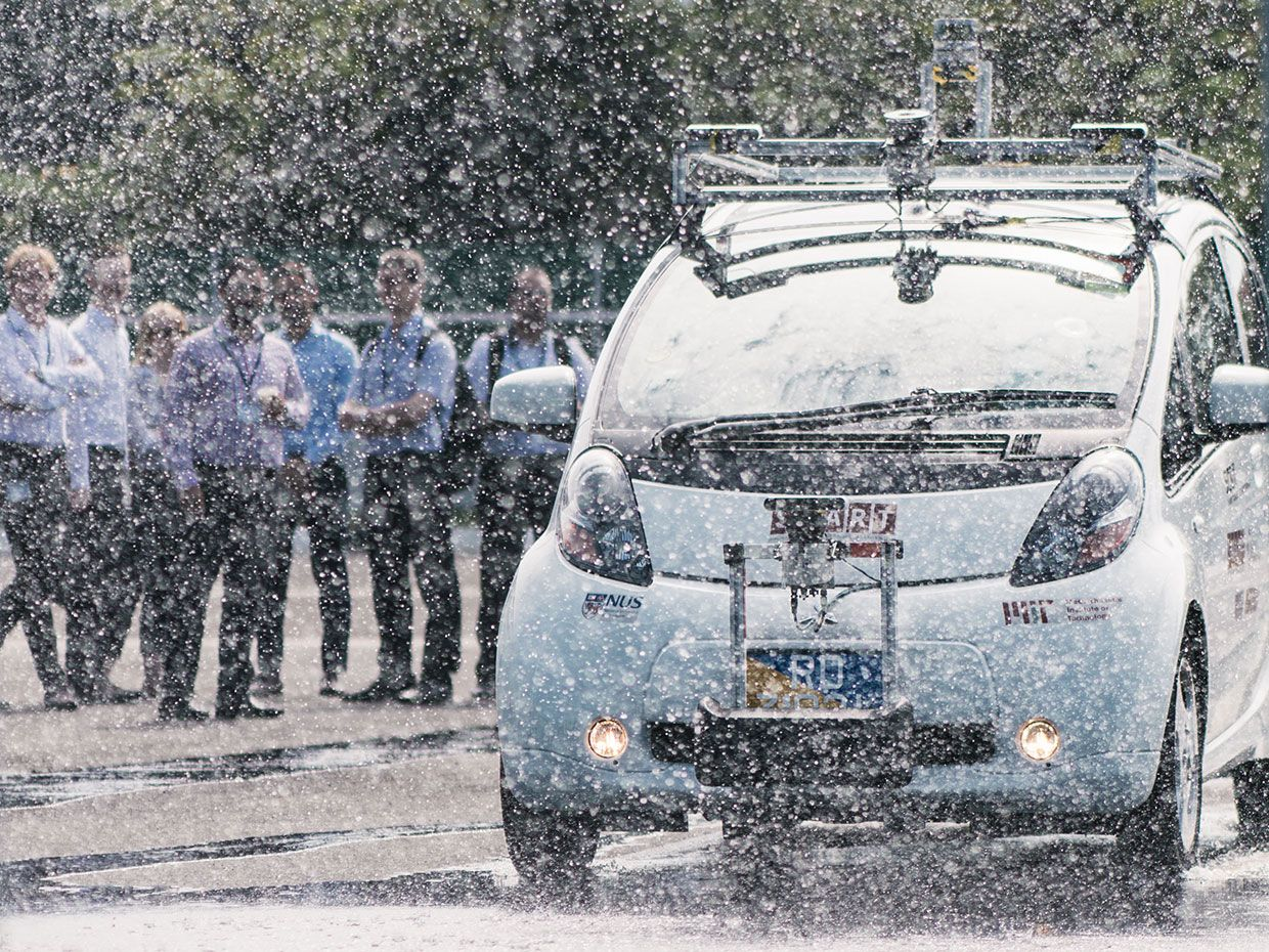 A photo shows a white self-driving car obscured by rain coming from nozzles above it, with people standing in the background to watch.