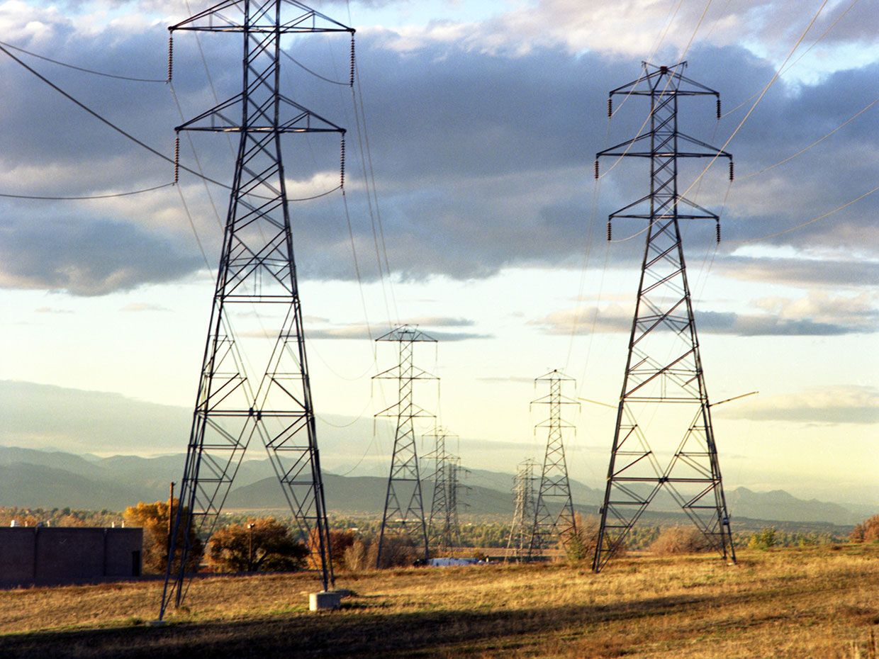 A photo shows high-voltage transmission lines crossing an open field.