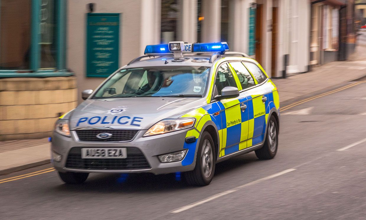 A Police car with blue lights flashing in Norwich, Norfolk, England, Britain, UK