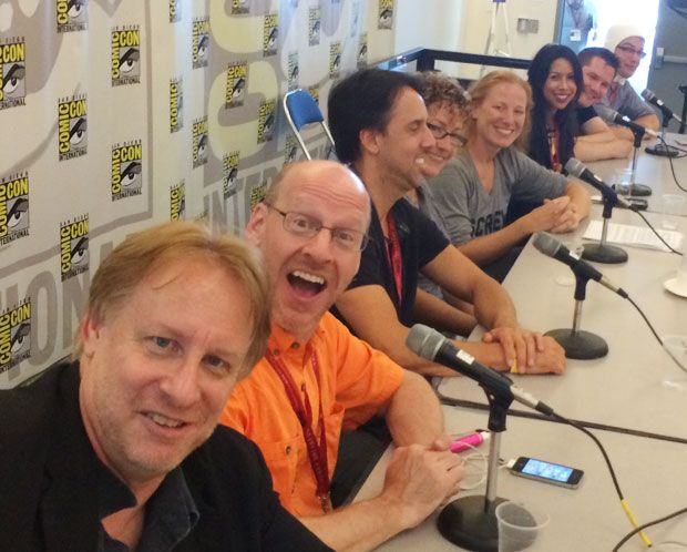 A row of 8 smiling people sitting at a table with a San Diego Comic backdrop behind them