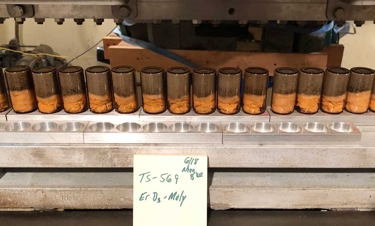 A row of orange tinted powdery samples sitting in the bottom halves of a row of transparent cylinders