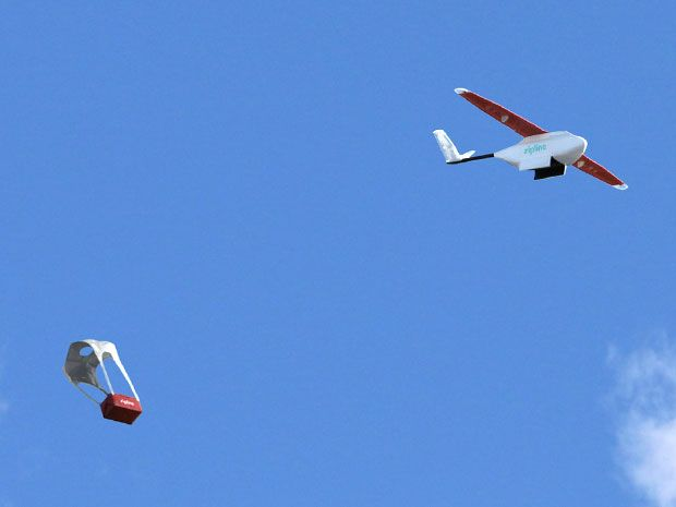 A small fixed-wing drone flies through the sky, and a small package drops slowly down to earth with a parachute attached.