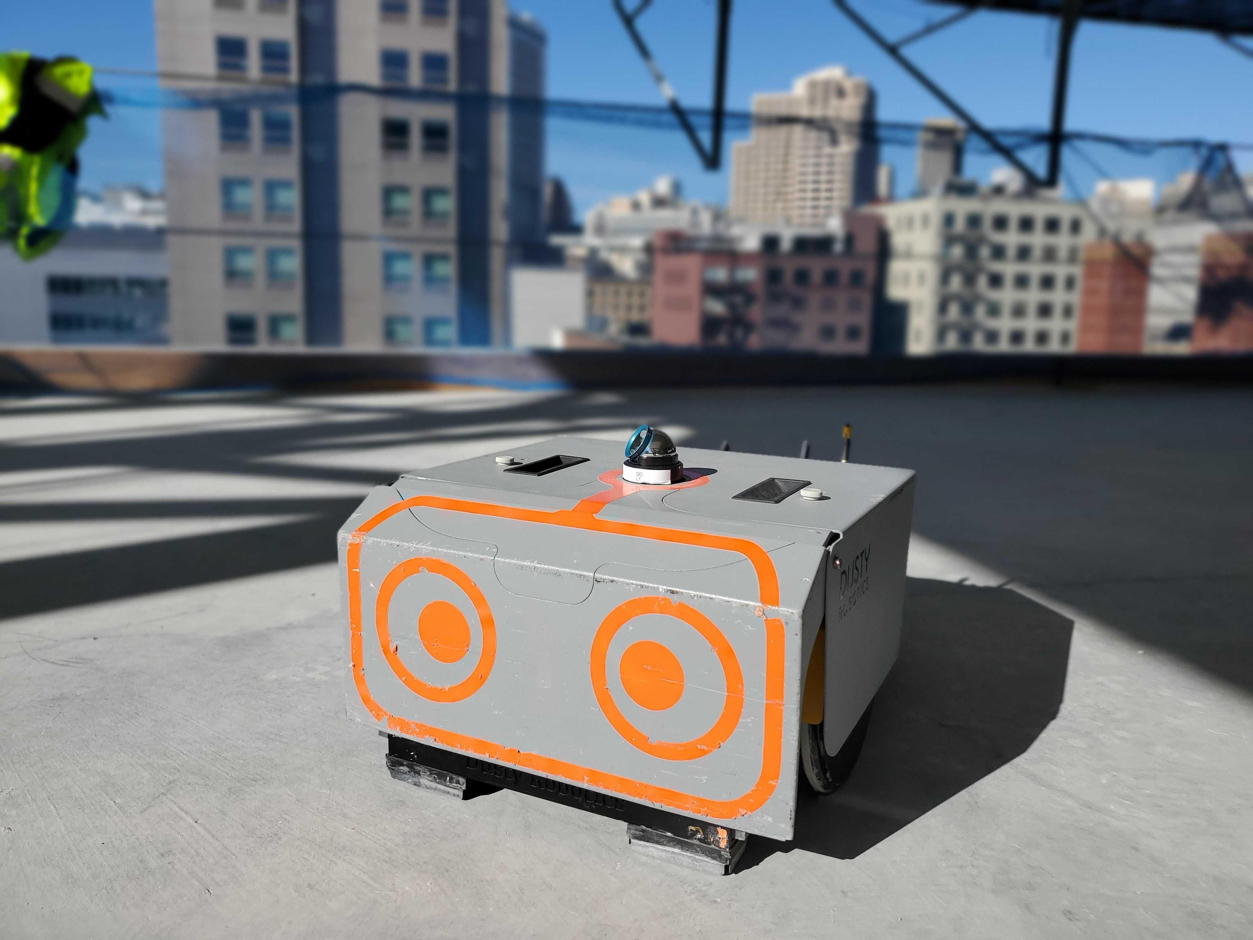 A small rectangular robot with large orange cartoon eyes on a construction site