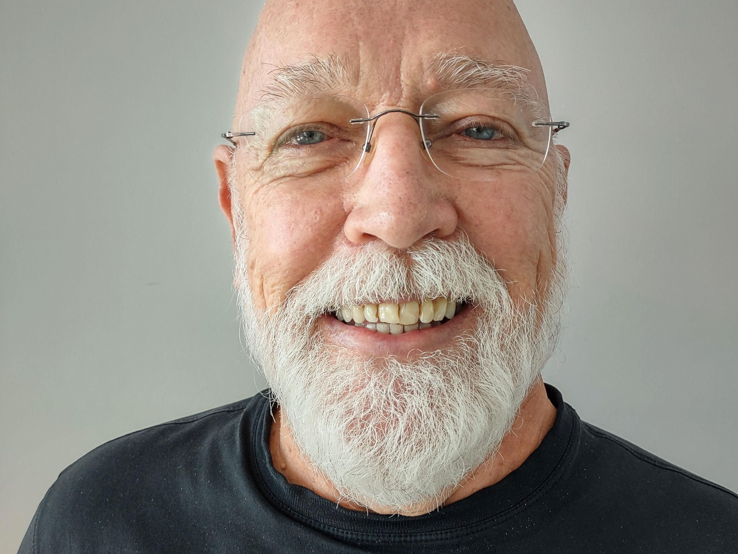 A smiling man with a white beard.