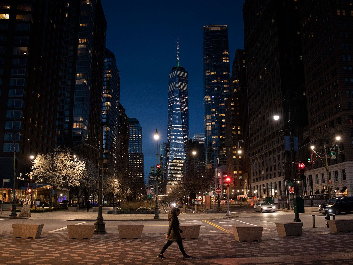 A solitary woman is seen walking in the foreground of the World Trade Center at night, New York, March 24, 2020