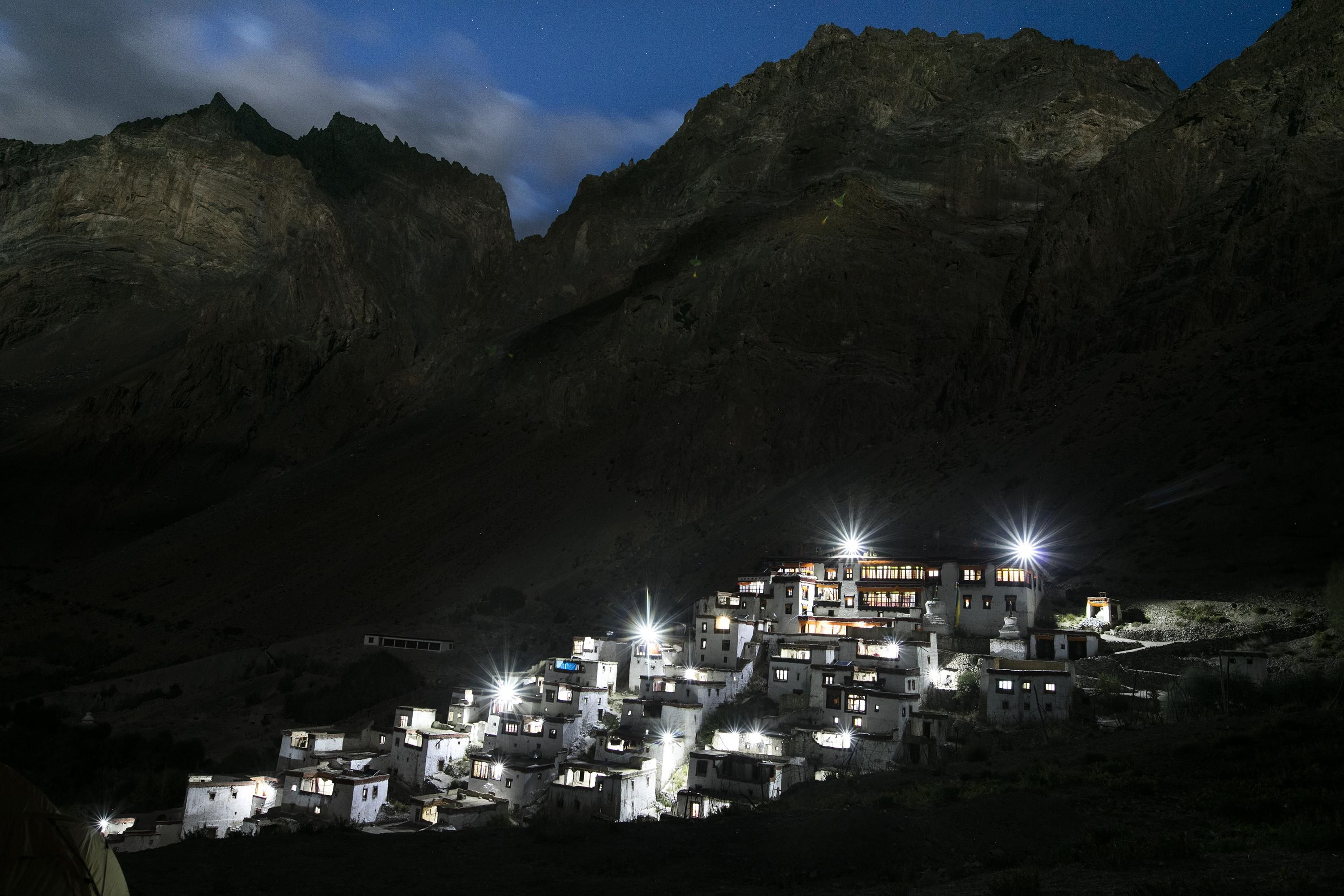 A village lit up with lights on the side of a mountain.