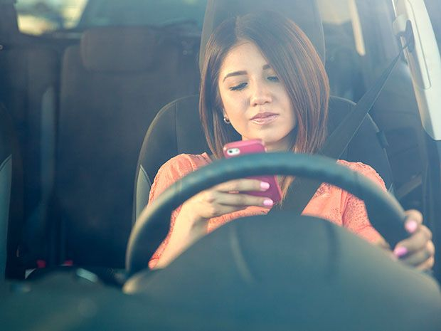 A woman behind the wheel of a car looking at a smartphone