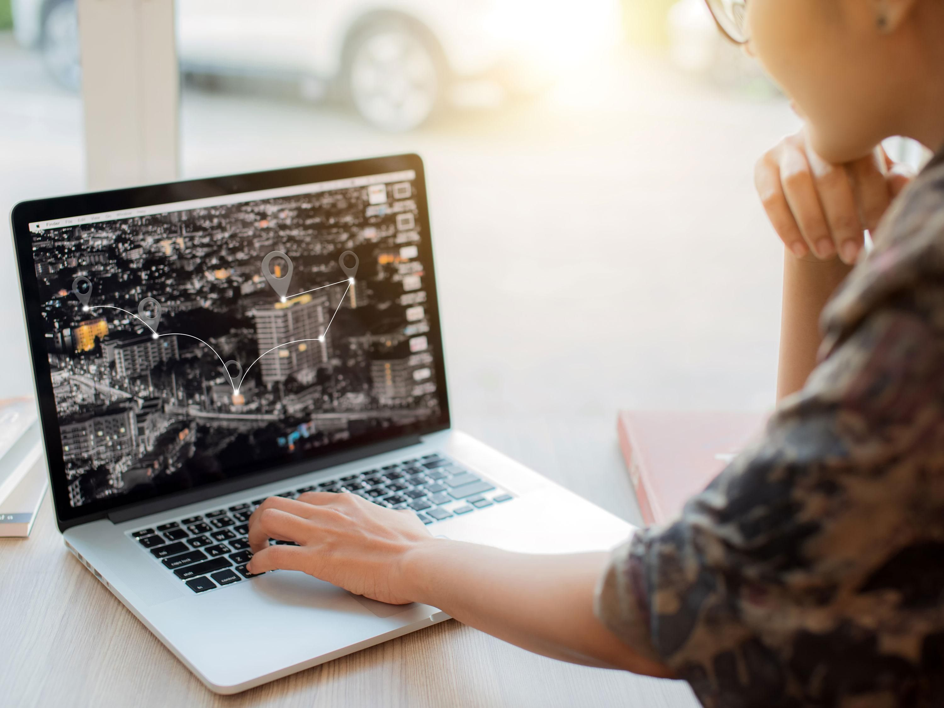 A woman looks at a map on computer screen with location icons