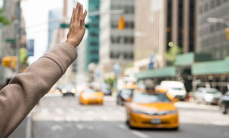 A woman's hand hails a taxi.