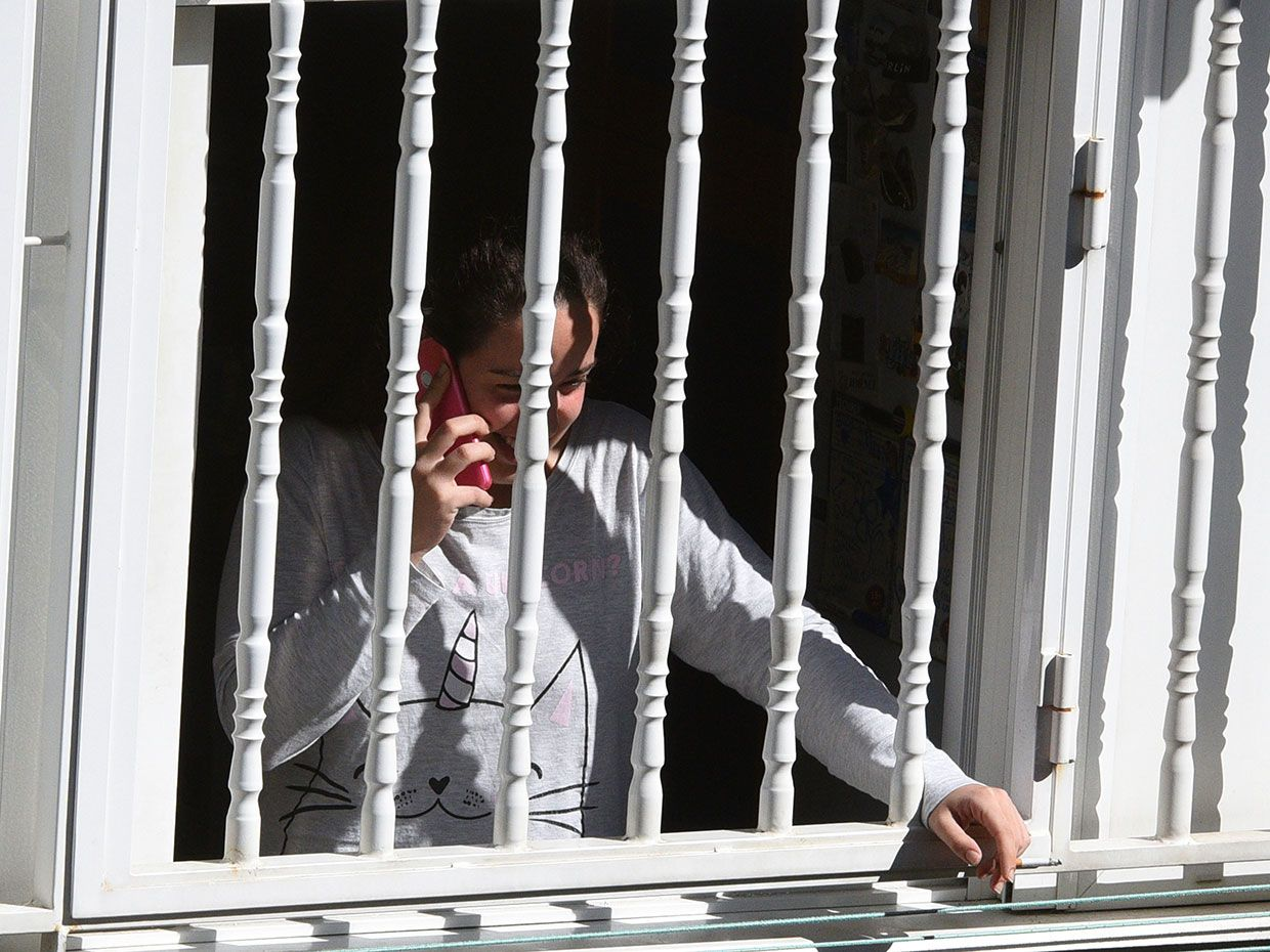 A woman talks on a mobile phone from inside her home during the lock- down amid coronavirus threat in Madrid