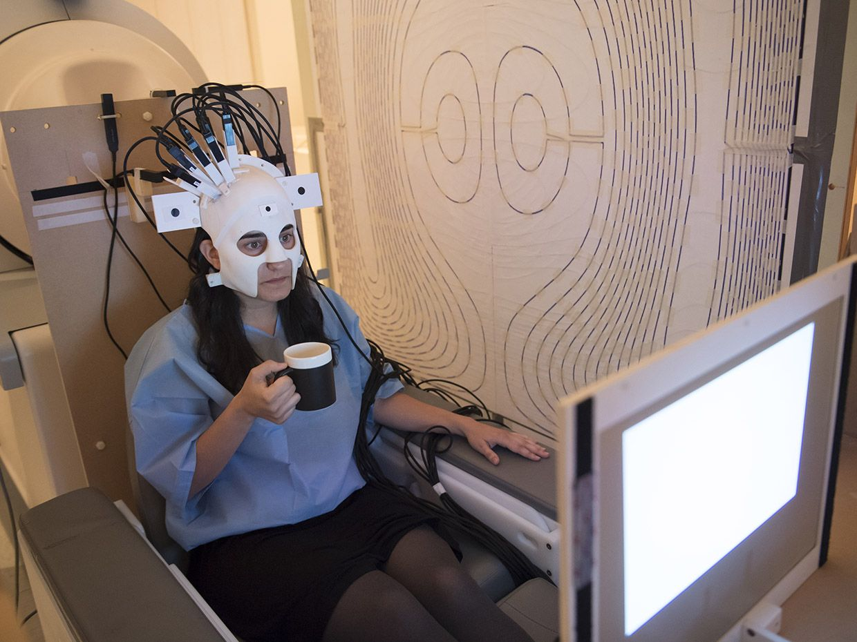 A women with a wearable scanner on her head drinking coffee