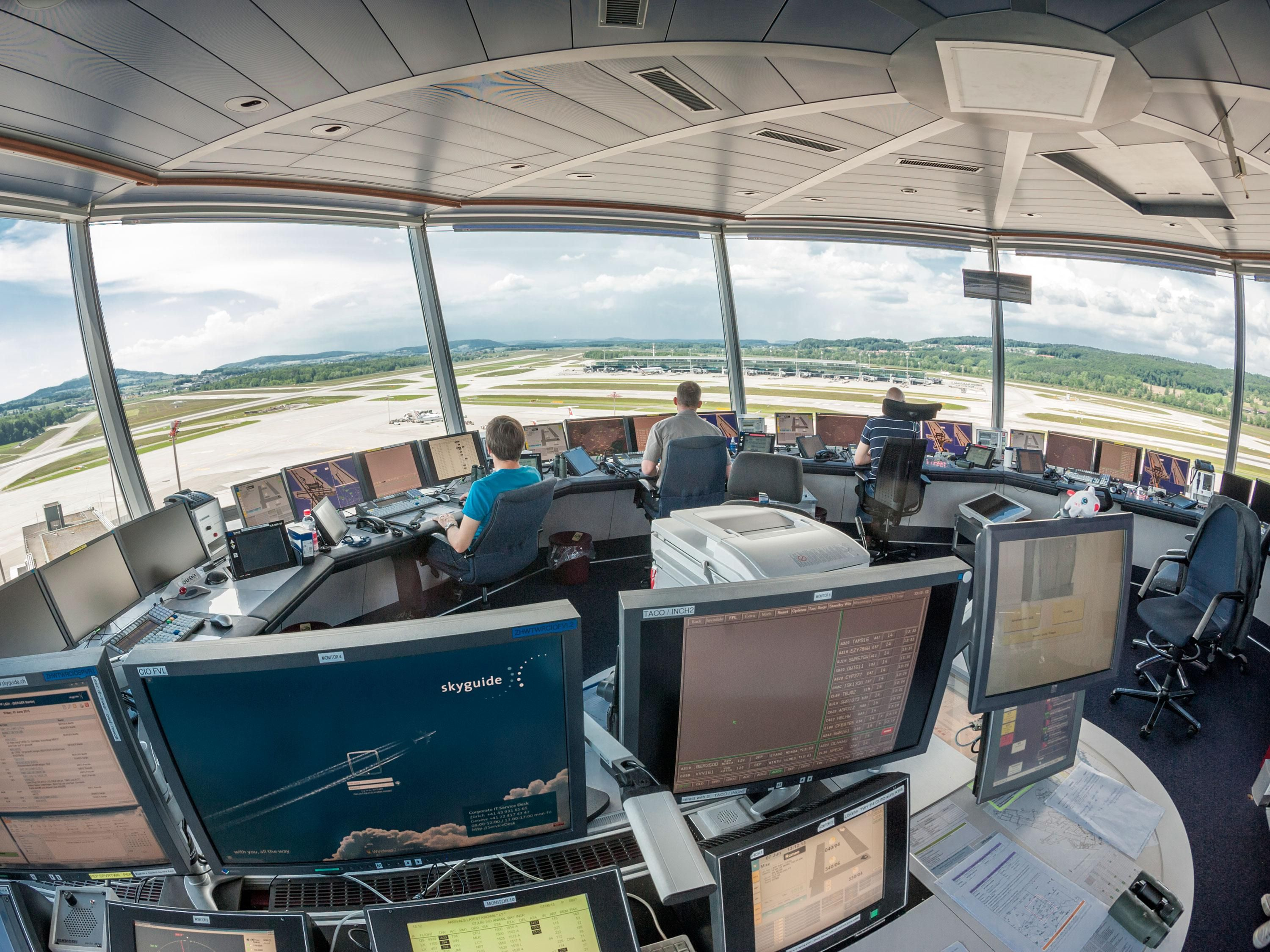 Air traffic controllers in a control tower monitoring the airfield.