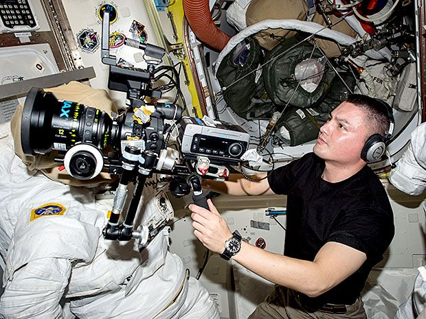 An astronaut floats inside a space station with a sophisticated camera.