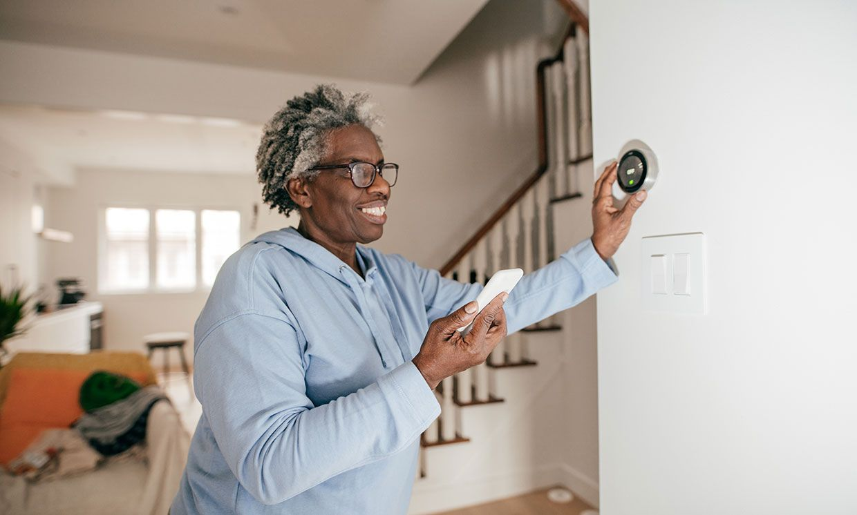 An elderly lady using smart devices in her home.