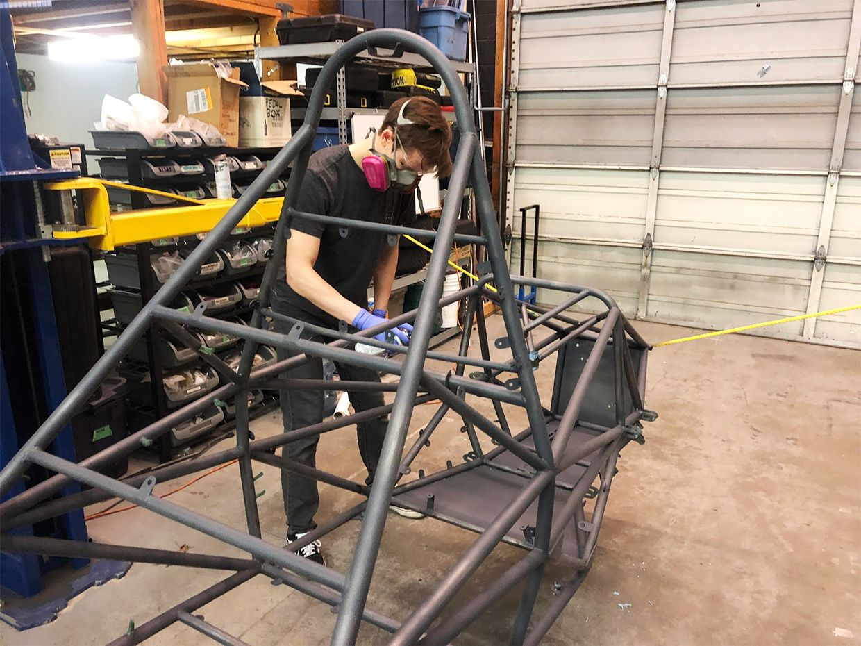 An image of Jules Pare painting the car's frame.