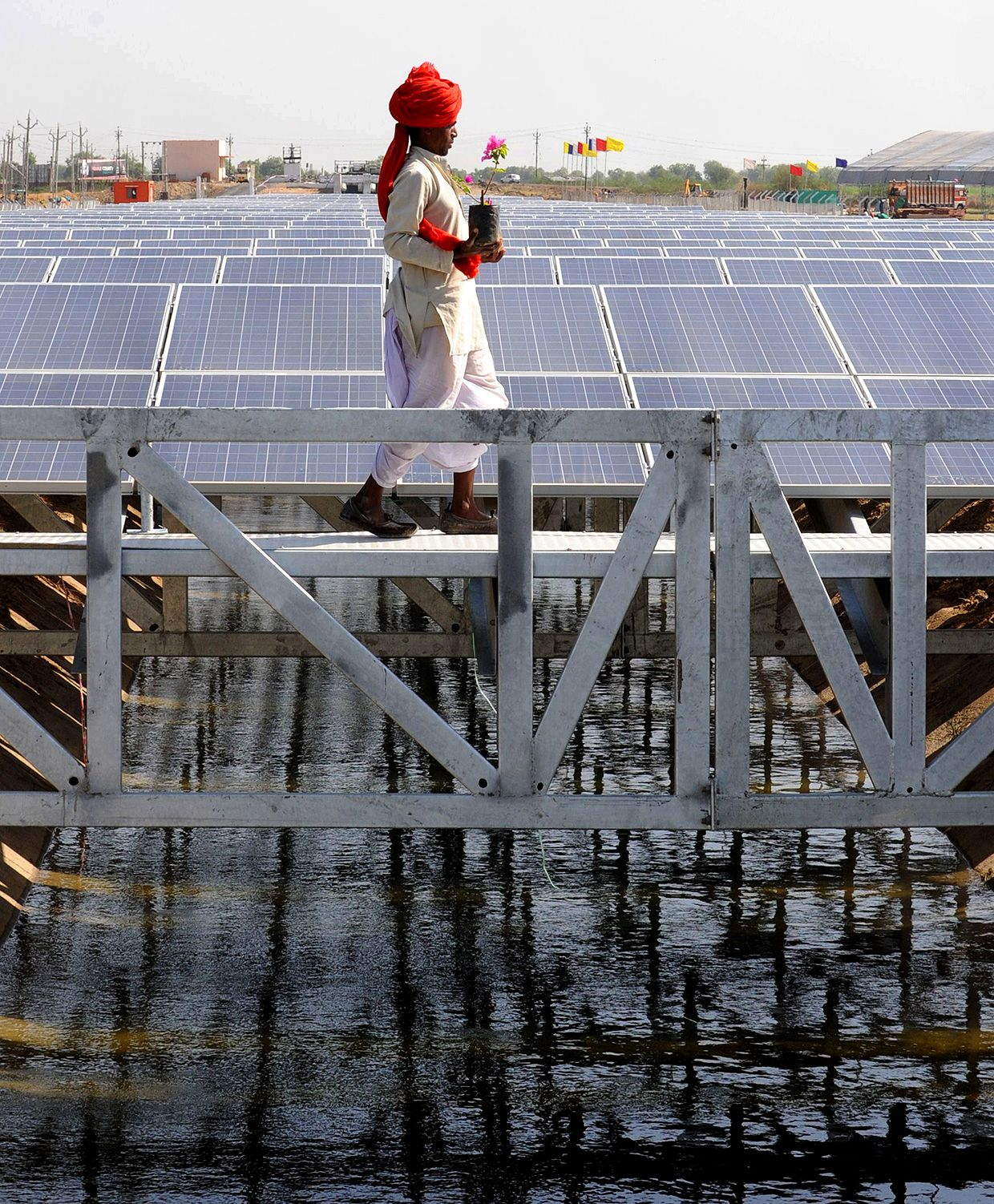 An Indian worker crosses solar panel canal in India.