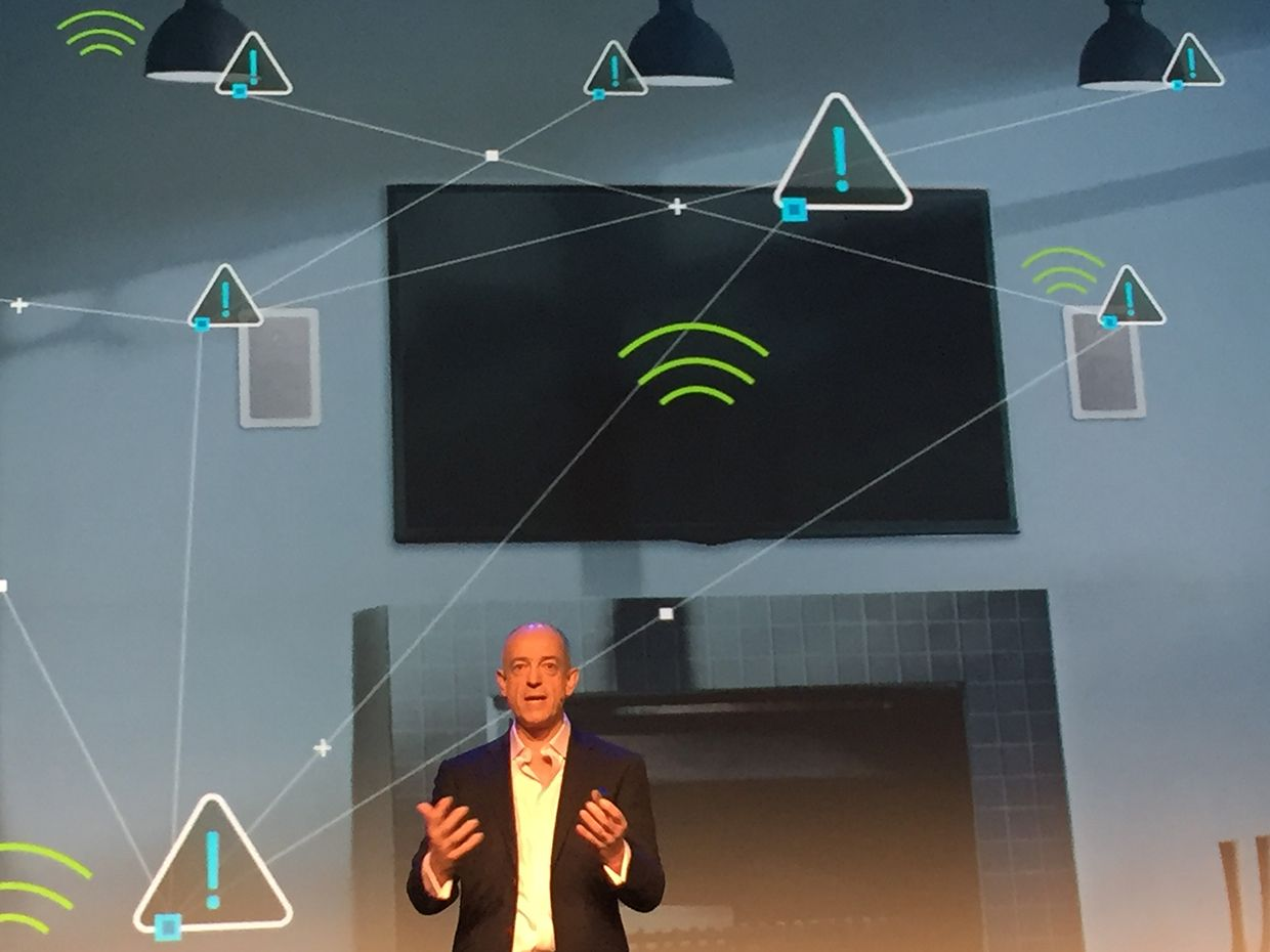 ARM CEO Simon Segars on a stage in front of a background indicating the internet of things